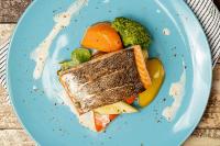Refeição proteica com salmão grelhado e legumes salteados.